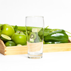Fresh green vegetables and fruits and glass