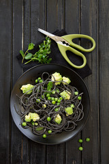 Cuttlefish ink spaghetti with broccoli and green peas.