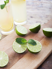 Fresh limes and lemonade on wooden background