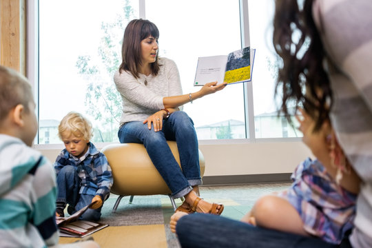 Teacher Reading Book To Students In Library
