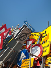Different Dutch traffic signs against a blue sky