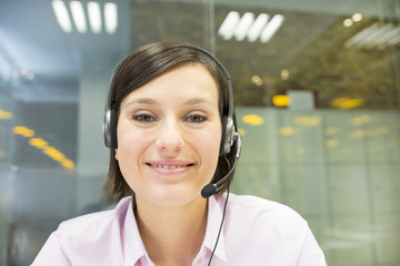 Businesswoman in the office on videoconference, headset, Skype