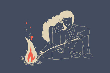 Young man and beautiful girl in love sitting near fire