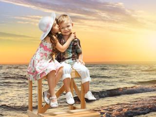 little girl kissing boy on sea landscape at sunset