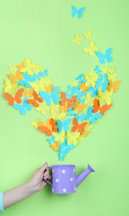 Paper butterflies fly out of watering can