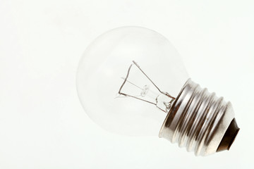 small transparent incandescent light bulb on white surface