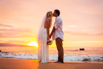 Married couple, bride and groom, kissing at sunset on beautiful