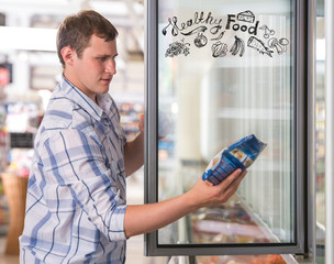 Young handsome man thinking of healthy food while shopping at gr