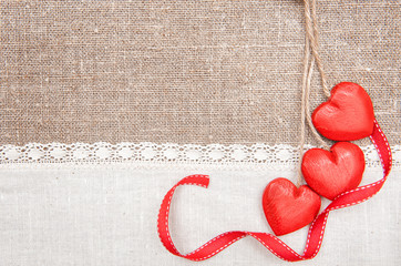 Wooden hearts, ribbon and linen cloth on the burlap