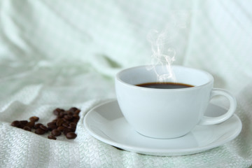 Coffee cup and beans on silk tablecloth