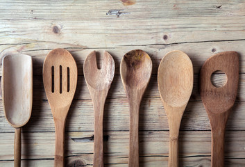 Row of assorted old wooden kitchen utensils