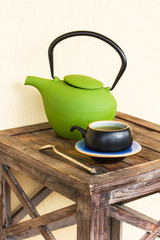 Green tea in cup and teapot on wooden table