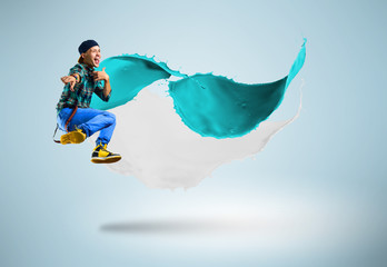 young male dancer jumping with splash of paint