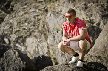 Handsome young man sitting on rock