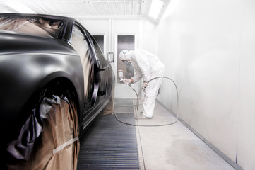 worker painting a black car in a special garage