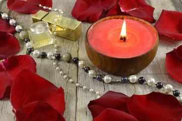 Red candle with jewelry on wood