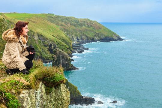 Woman sitting on rock cliff looking to ocean Co. Cork Ireland