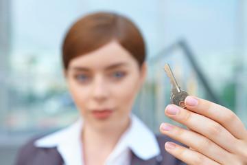 Businesswoman holds door key.