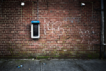Foto op Canvas Graffiti Grungy urban wall with an old payphone on it
