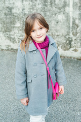 Outdoor portrait of a beautiful little girl in a grey coat