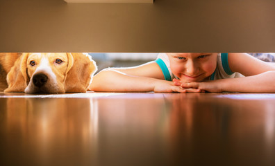Fototapete - Boy with doggy friend looks under the bed