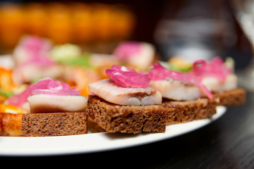 Herring canapes in plate, close-up