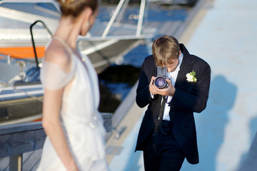 Groom shooting his bride with an old camera