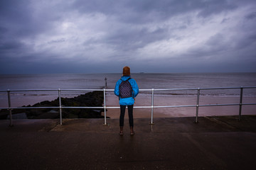 Hiker standing by the sea on a stormy day