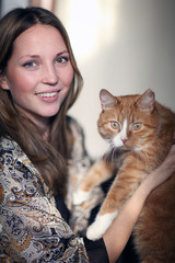 portrait of a beautiful girl with a red cat