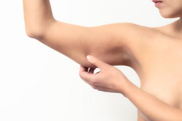 Frau prüft den schlaffen Muskel an ihrem Arm Fototapete