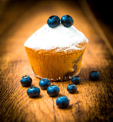 Wall Mural - Blueberry muffins with powdered sugar on wood table
