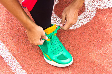 Tying sports shoe on the running track