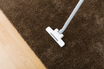 Brown carpet with vacuum cleaner in living room