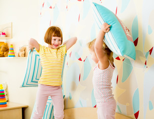 kids sisters playing with pillows in the bedroom