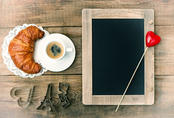 coffee with croissant, blackboard and heart decoration