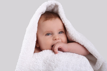 smiling cute baby in a white towel after bathing