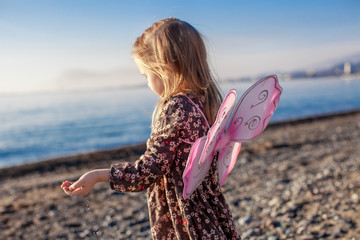Adorable Little girl having fun on the beach in a winter sunny
