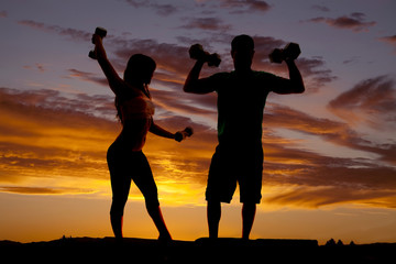 silhouette couple with weights flex