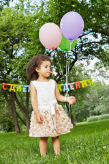 Little girl stands in park, holding three air balloons