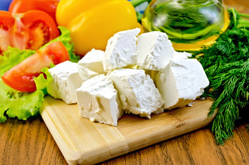 Feta cheese on the board with vegetables and salad