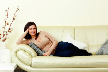 Young happy smiling woman lying on the sofa at home