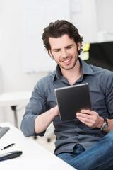 mann sitzt am schreibtisch und liest am tablet