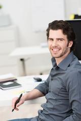 junger mann am arbeitsplatz im büro