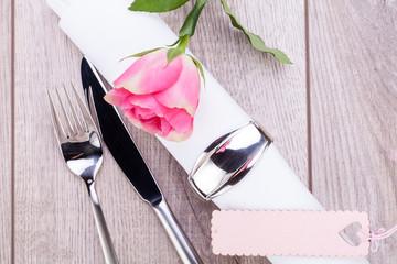 romantisch gedeckter tisch mit silberbesteck und einer rose