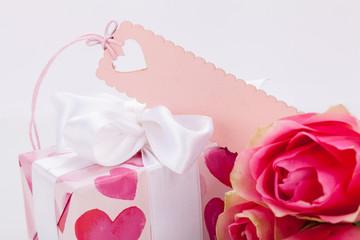 kleines verpacktes geschenk mit herzen und rosen in pink