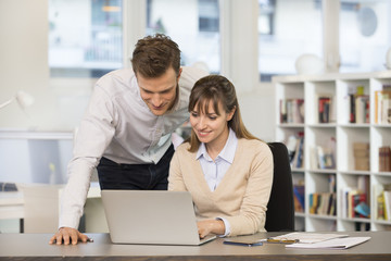 Smiling business team working on computer in office