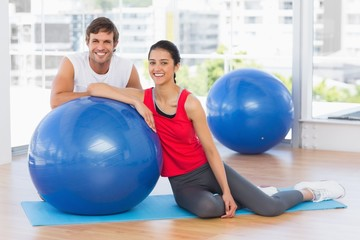 Smiling fit young couple with exercise ball at gym