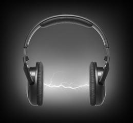 Headphones and lightning on black background