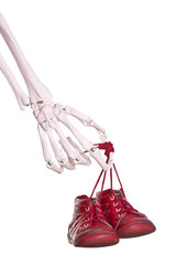 skeleton hand holding old red baby shoes