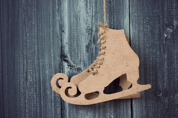 Pair of carton figure skates over grey wooden background